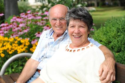 Älteres Ehepaar im eigenen Garten dank Immobilienfinanzierung